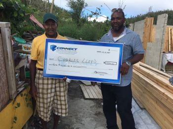 Mr Charles Lloyd is gifted with a cheque for $1000 by local businessman Mr Clive George, right. Photo: Provided