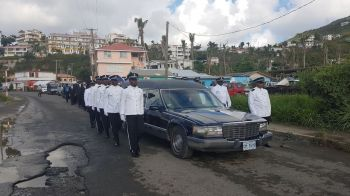 Police ranks flank the hearse bearing the casket of former legislator Omar W. Hodge. Photo: VINO
