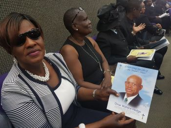 A woman flashes a booklet in tribute to late legislator Omar W. Hodge. Photo: VINO