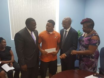 Kadeem Hodge, centre, owner of the butcher shop 'Hodges Chophouse', receives his cheque. Photo: VINO