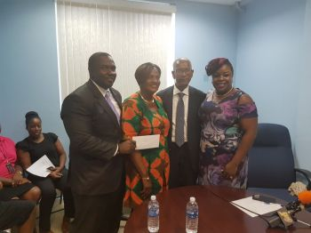 Prominent farmer Ms Moviene F. Fahie receives her cheque. Photo: VINO
