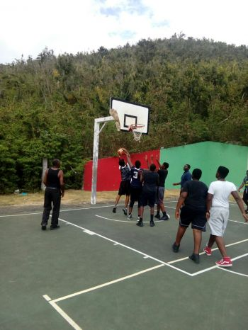 Raphael E. Singh (with ball) tries to score from under the basket for Hotter Than July. Photo: Team of Reporters