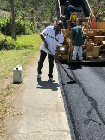 Third District Representative Hon Julian Fraser RA lending a hand with leveling the asphalt on the road in his district today, March 25, 2018. Photo: Team of Reporters