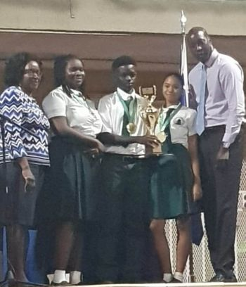 Acting Chief Education Officer, Connie E. George (left), and Honourable Myron V. Walywn (AL), (far right) Minister for Education and Culture, presenting a trophy to the runners-up Ra'naa James, Chad R. Willock, and Aniyah Wilkinson of the St Georges Secondary School debating team. Photo: Team of Reporters