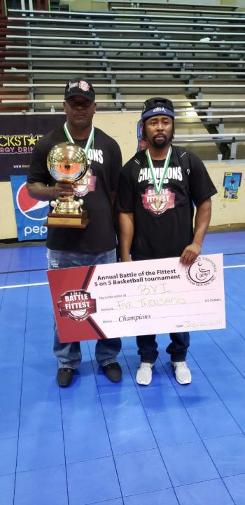 Team Coach, Ronald Simmonds (Right) and Assistant Coach, Trevor M. Stevens (Left) displaying the winning cheque. Photo: Team of Reporters
