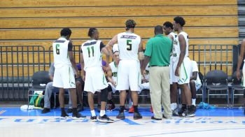 Coach of the Senior National Basketball Team competing at the Paradise jam Tour in St Thomas, US Virgin Islands, Byron Brewley aka 'Bash' (in green top) speaks to his players during one of the games. Photo: Team of Reporters