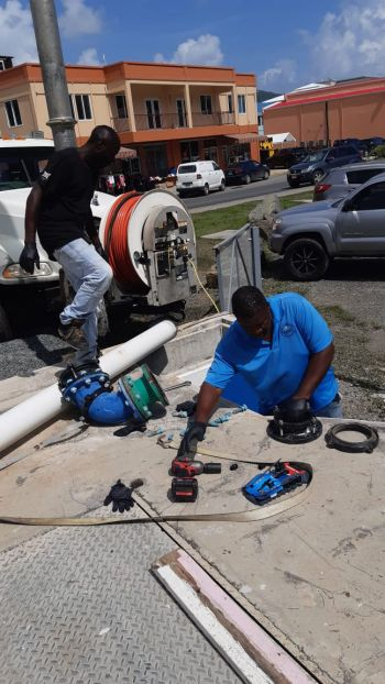 Servicemen of the Water and Sewerage Department repair the pipework at the Road Town Pump Station. Photo: Team of Reporters