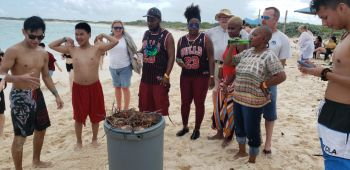Patrons of Anegada Lobster Festival 2019 gather around a barrel of lobsters. Photo: VINO