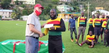 Lion Heart skipper Dwayne Smith, right, collects $2000 on behalf of his team for finishing as runners up of the 2020 BVIFA Festival Cup. Photo: VINO