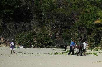 Paramedics escorting the injured female from the beach after approximately twenty minutes of attending to her injured right leg on the beach. Photo: VINO