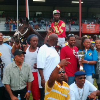 In the winner's circle! St Moose owner James Bates (red shirt) is presented with the winner's trophy by President of the VI Horse Owners' Association Karen B. Smith Aaron (blue shirt). Photo: Charlie E. Jackson/VINO