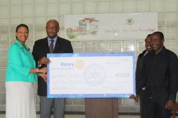 Minister for Health and Social Development Honourable Ronnie W. Skelton after receiving the cheque immediately passed it on the BVIHSA's CEO Ms Darlene Carty-Baptiste, left and Chairman Bishop John I. Cline. Photo: VINO