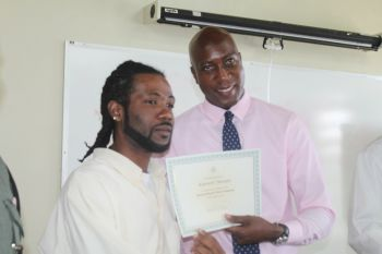 An inmate receiving his certificate from Minister for Education and Culture Hon Myron V. Walwyn. Photo: VINO