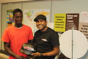 TRW's Devon Joseph (right) presents a helmet to one of the participants. Photo: Provided