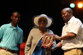 Ms Grace Vanterpool receiving her plaque of honour from Mr Blyden in presence of PRO Jerrell A. George. Photo: VINO