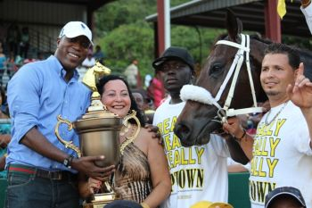 Owner of Really Uptown Violet 'Letty' Hodge receives the winning trophy for the feature race from Minister for Education and Culture Hon. Myron V. Walwyn (left). Photo: VINO