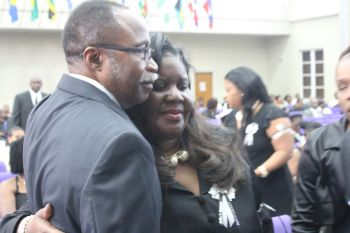 Honourable Julian Fraser RA (R3) consoles Mrs Oleanvine Pickering-Maynard during the service. Photo: VINO