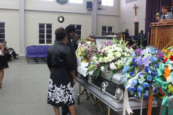 The casket bearing the earthly remains of Collin V. Maynard almost covered in floral tributes. Photo: VINO