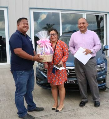Parts manager of Tortola Auto Group Tirsol Tuppil Jr, left, presents Michelle Vitug and Arnel Soller for being among the first to purchase a Volkswagen vehicle from Tortola Auto Group. The couple bought a Jetta sedan. Photo: VINO