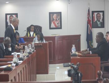Premier and Minister of Finance Dr The Honourable D. Orlando Smith (AL), standing left, makes a statement while Opposition Leader Honourable Andrew A. Fahie (R1), right, listens attentively in the House of Assembly on March 1, 2018. Photo: VINO