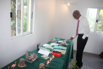 Premier and Minister for Tourism, Dr The Hon D. Orlando Smith (AL) browses through the informative items available at the Sage Mountain National Park Visitor Centre. Photo: VINO