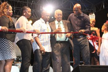 Hon O'Neal being assisted with the cutting of the ribbon to ceremonially declare the Festival open. To his left is Minister for Education and Culture Hon Myron V. Walwyn and to his right are Chairperson of the Virgin Gorda Festival Committee Sasha D. A. Flax and Chairperson of the VI Festival and Fairs Committee Kishma A. Baronville. Photo: VINO