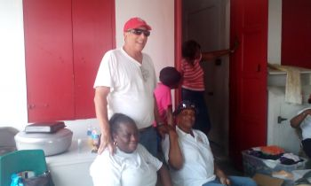 Geoffrey H. Brooks (red cap), Chairman of the Board of Directors for BVI Red Cross, assisting the volunteers with the package distribution. Photo: VINO