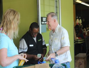 A customer giving one of the differently abled participants money after receiving a token for shopping at RiteWay. Photo: VINO
