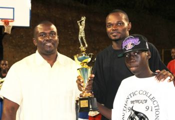 Kennedy Bass (centre) collects his MVP trophy from Hon. Marlon A. Penn. Photo: Reuben J. A. Stoby/VINO