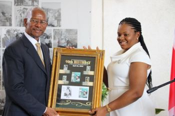 Premier Dr The Hon D. Orlando Smith with one set of the collection of stamps for the Queen's 90th birthday. With him is Postmaster Pasha Stoutt. Photo: VINO