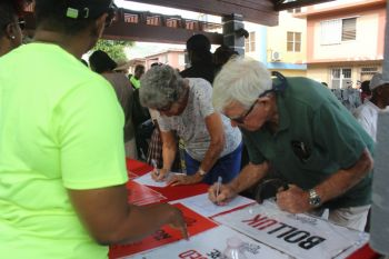 Peter Haycraft and his wife Mrs Haycraft signing the petition. Photo: VINO