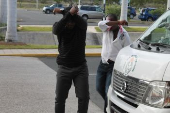 Two of the illegal immigrants hid their faces from the camera at the Terrence B. Lettsome International Airport on March 21, 2013. Photo: VINO
