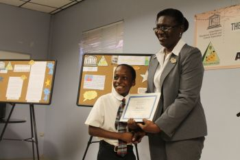 Jhared Jones of Agape Total Life Academy was the 1st place winner in the Junior category. He received his prize of a certificate and a Kindle Fire from Ag. Deputy Secretary in the Ministry of Education and Culture Mrs Prudence Mathavious. Photo: VINO