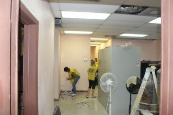 Volunteers at work during the painting project yesterday at the Library Services Department. Photo: VINO