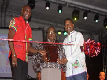 Honourable Myron V. Walywn (left) and Chairman of the Virgin Islands Festival and Fairs Committee (VIF&FC), Mr Trefor A. Grant (right) presenting a plaque to Honourable Alvera Maduro-Caines (R6) (centre) for her dedication in the cultural development of the Emancipation Festival throughout the years. Photo: VINO