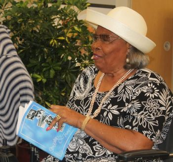 Mrs Eileene L. Parsons, one of the participants during the process of the information gathering for the writing of the book. She takes her first brush through of the copy that was presented to her at the launch ceremony. Photo: VINO