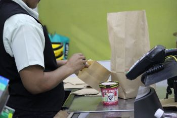 A cashier at RiteWay supermarket fills paper bags with goods bought by a customer. Photo: VINO