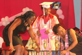 Needing two pairs of extra hands for her awards! The Valedictorian for Althea Scatliffe Primary School this year was Kiymeiah Millington, who was also the top student in Mathematics, English and Social Studies. Photo: VINO