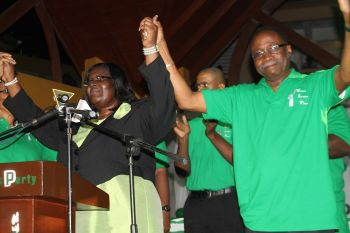 Virgin Islands Party Chairman Hon Julian Fraser RA raises the hand of Seventh District candidate Oleanvine Pickering-Maynard at The Stickett in Long Look on May 18, 2015. Photo: VINO