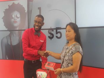 Andy A. Jeffers, Marketing Executive at Digicel making a presentation to Brenda B. Sahagun for being the first customer to enter the door following the cutting of the ribbon. Photo: VINO