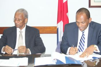 Premier and Minister of Finance Dr. the Honourable D. Orlando Smith (left) along with the Minister for Communications and Works Honourable Mark H. Vanterpool placed their signatures to the agreement on the behalf of the people, the BVI Ports Authority and Government of the Virgin islands. Photo: VINO