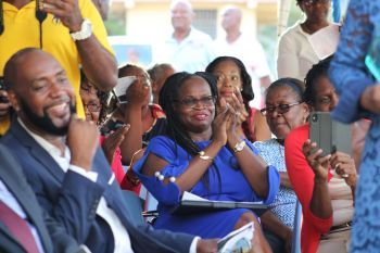 Newly appointed Principal of Elmore Stoutt High School (ESHS), Ms Vanessa K. Garraway, (centre, in blue) cheers as retired educator Ms L. Adorothy Turnbull is honoured. Photo: VINO