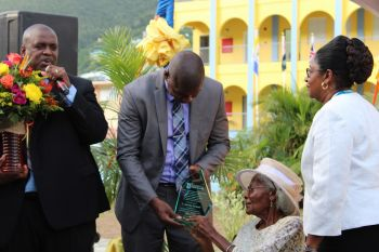 Minister for Education, Culture, Youth Affairs, Fisheries and Agriculture, Dr The Honourable Natalio D. Wheatley (R7) presents his former teacher Ms L. Adorothy Turnbull with a plaque on behalf of the Government of the Virgin Islands in recognition of her faithful service, loyalty and devotion to the education system of the territory. Photo: VINO