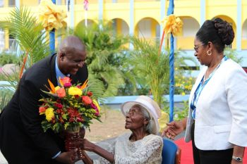 Premier and Minister of Finance Honourable Andrew A. Fahie (R1) gives retired educator Ms L. Adorothy Turnbull 'her flowers', saying not often do you find an educator who has taught for 50 years and is still alive to share the moment with. Photo: VINO