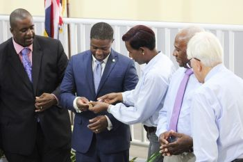 Purchasing Manager of Newton Construction Company, Ms Amorrell Newton, 3rd from left, symbolically hands over the key to the Enis Adams Primary School to Second District Representative, Hon Melvin M. Turnbull, who then passed it on to Premier and Minister of Finance Hon Andrew A. Fahie (R1), who turned it over to Education Minister Dr The Hon Natalio D. Wheatley (R7), who gave it to Acting Chief Education Offficer, Connie E. George, who then presented it to Principal of the school Ronda D. Smith-Thomas. MS Newton had received it from Mr Hesketh Newton, who collected it from benefactor Mr Peter Haycraft, right. Photo: VINO