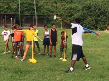 President of the BVI Athletics Association, Mr Steve Augustine shows the children how to throw the Javelin. Photo: Provided