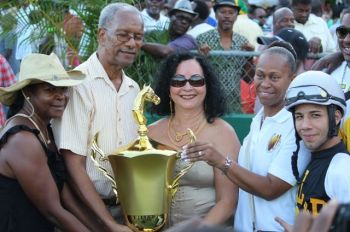 Letty Hodge (centre) receives the winning trophy flanked by Premier Dr. The Hon. D. Orlando Smith (left) and President of the VI Horseowners' Association Karen Smith-Aaron (right) following the feature race of the first leg of the VI Triple Crown Challenge. Photo:VINO/File