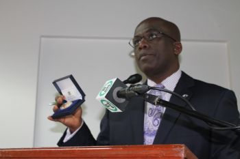 Mr Kedrick E. Malone displays the Medallion to members of the media on Monday January 14, 2013 when he highlighted the strides made by the BVI London House in 2012 and outlined some of the tasks for 2013. Photo: VINO