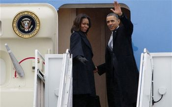 President Barack Obama, accompanied by first lady Michelle Obama, waves prior to boarding Air Force One at Andrews Air Force Base before traveling to South Africa. They were joined by former President George W. Bush, his wife Laura and former first lady Hillary Clinton. Former Presidents Bill Clinton and Jimmy Carter are traveling separately to South Africa. Photo: AP Photo/Jose Luis Magana