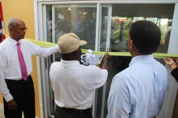 Mr Denville Hodge cuts the ribbon to signal the opening of the Sage Mountain National Park Visitor Centre as Premier Dr The Hon D. Orlando Smith (left) and Deputy Premier Dr The Hon Kedrick D. Pickering look on. Photo: VINO